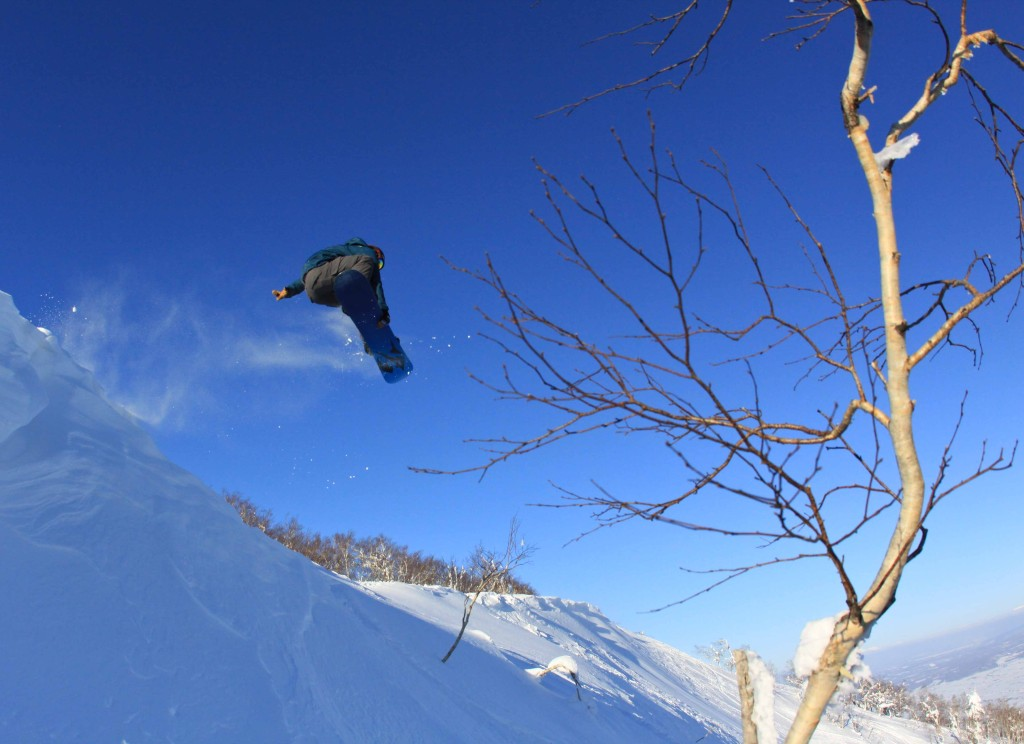 Professional snowboarder Alex Deibold jumping off the top of a mountain spinning and grabbing in front of a tree in Furano Japan